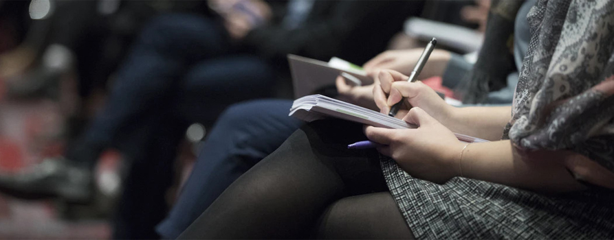 person taking notes at a conference