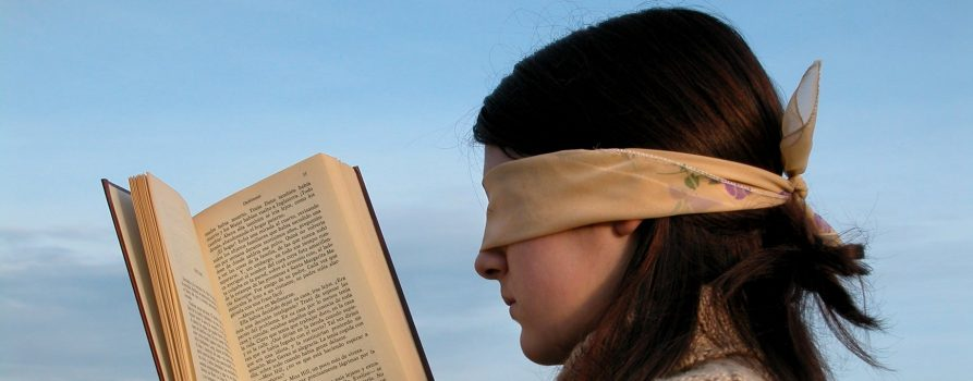 blindfolded girl reading book