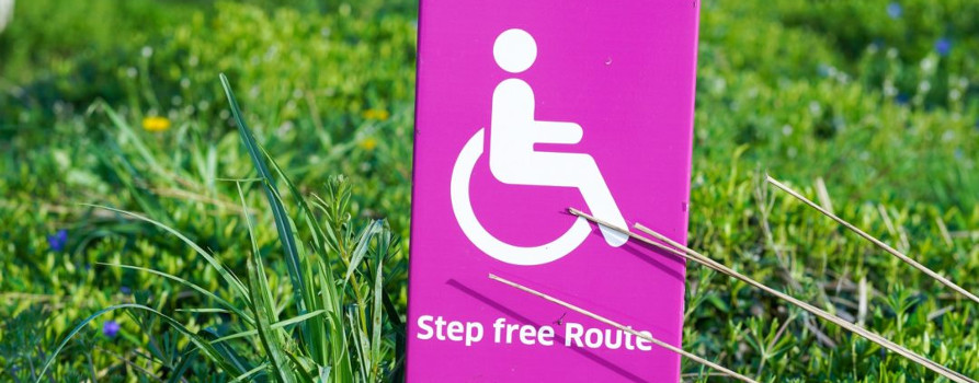 Pink sign on grass saying Step Free Route with wheelchair image