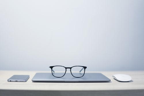 CLosed laptop on desk with reading glasses resting on top