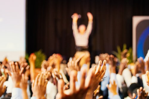 Blurred image of audience with raised hands