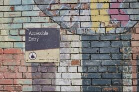 brick wall with a sign saying Accessible Only