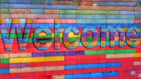 Mulit-coloured brick wall with the words Welcome