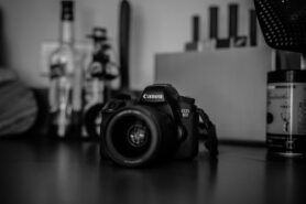 Canon camera on desk photographed in greyscale